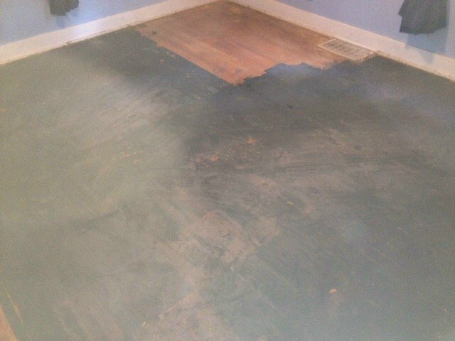 a hardwood floor with a big black stain on it